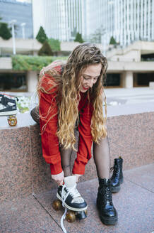 Young woman putting on roller skates in the city - KIJF02896