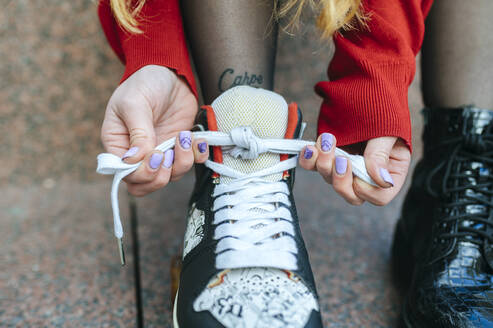 Close-up of young woman putting on roller skates - KIJF02899