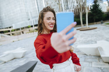 Smiling young woman taking a selfie in the city - KIJF02905