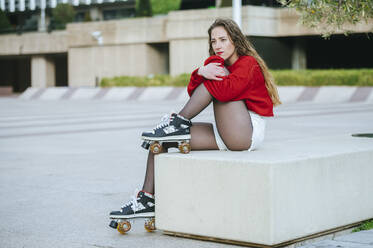 Young woman with roller skates sitting on a wall in the city - KIJF02908