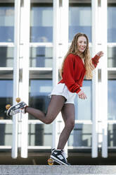 Portrait of happy young woman balancing on roller skates in the city - KIJF02914