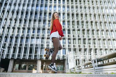 Portrait of happy young woman balancing on roller skates in the city - KIJF02917