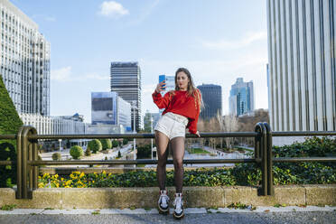 Young woman on roller skates taking a selfie in the city - KIJF02920