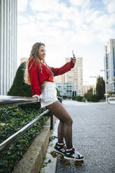 Smiling young woman on roller skates taking a selfie in the city - KIJF02923