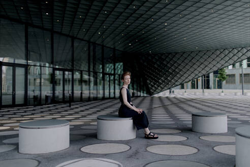 Elegant woman sitting on round bench in futuristic architecture - OGF00130