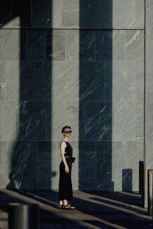 Red-haired woman with sunglasses, in front of stone wall with shadows - OGF00139