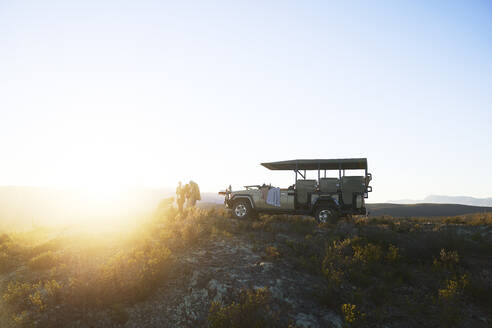 Safari tour group outside off-road vehicle on tranquil hill at sunrise - CAIF23940