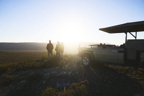 Safari tour group and off-road vehicle on hill at sunrise South Africa - CAIF24033