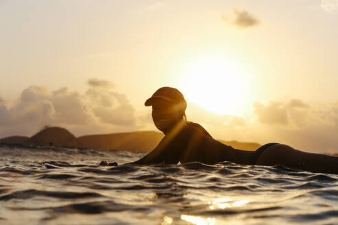 Female surfer lying on surfboard in the evening - CAVF74868
