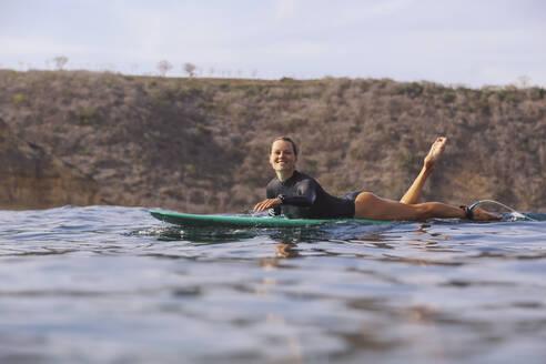 Happy woman sitting on surfboard in sea - CAVF74877