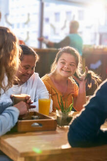 Young women with Down Syndrome talking in cafe - CAIF24344