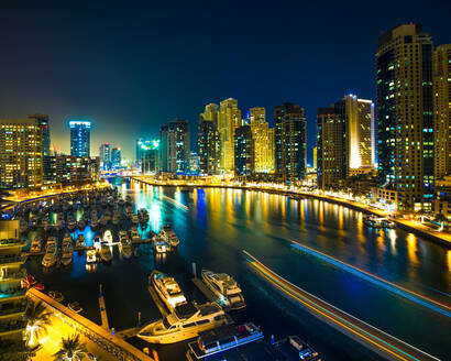 Night scene of city skyline and boats moored at harbour, Dubai - ISF23859