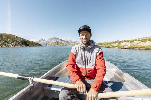 Young smiling man in a rowing boat, Lake Suretta, Graubuenden, Switzerland - HBIF00034