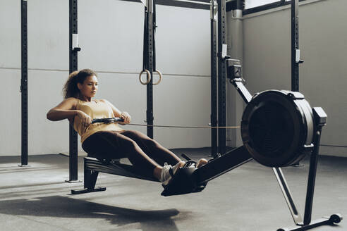Young woman exercising in gym with rowing machine - MTBF00353