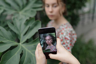 Picture on smartphone of a female teenager in Botanical Garden - OGF00161