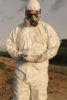 Man wearing protective suit and mask in the countryside holding seedling in glass case - ERRF02638