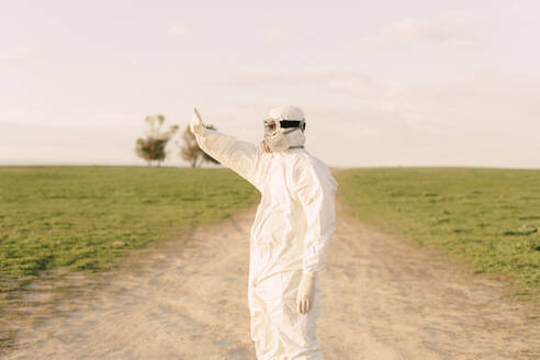 Man wearing protective suit and mask standing on dirt track in the countryside - ERRF02641