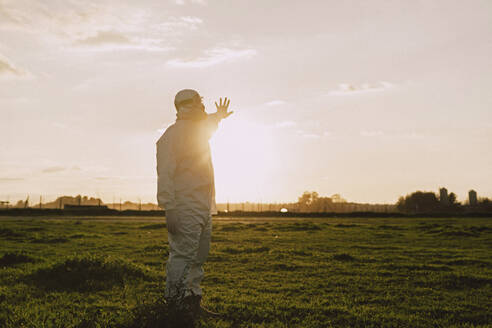 Man wearing protective suit and mask in the countryside at sunset - ERRF02647