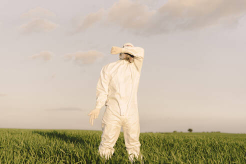 Man wearing protective suit and mask in the countryside covering his eyes - ERRF02650