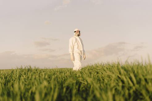 Man wearing protective suit and mask in a field - ERRF02653