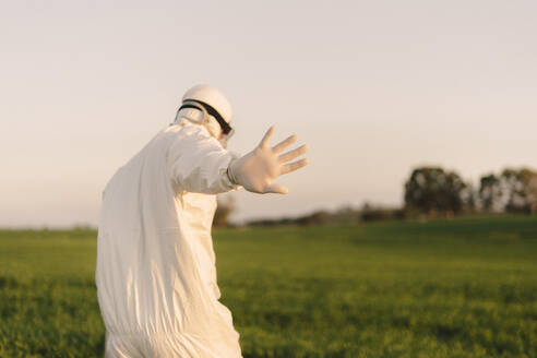 Rear view of man wearing protective suit in the countryside raising his hand - ERRF02674