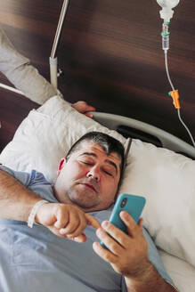 Patient lying in hospital bed using cell phone - LJF01345