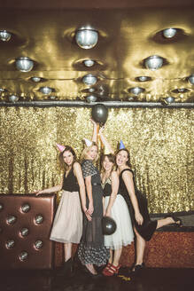 Portrait of four happy women wearing party hats in a club - HBIF00050