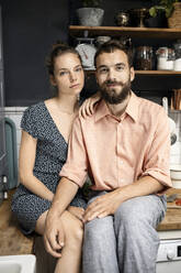 Young couple sitting on kitchen worktop, smiling - PESF01810