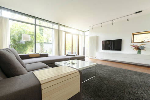 Modern living room in design house with large windows - SBOF02083