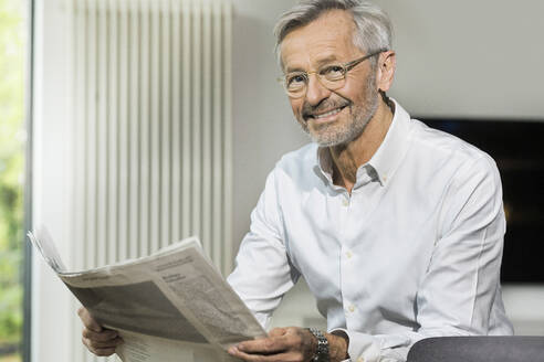 Portait of smiling senior man with grey hair in modern design living room reading newspaper - SBOF02092