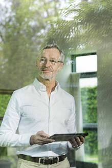 Senior man with grey hair in modern design living room holding tablet - SBOF02098