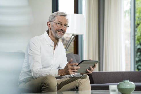 Smiling senior man with grey hair in modern design living room sitting on couch holding tablet - SBOF02101