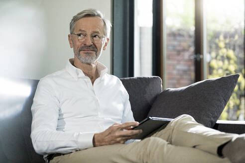 Senior man with grey hair in modern design living room sitting on couch holding tablet - SBOF02104