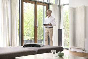 Senior man with grey hair in modern design living room standing at window holding tablet - SBOF02110