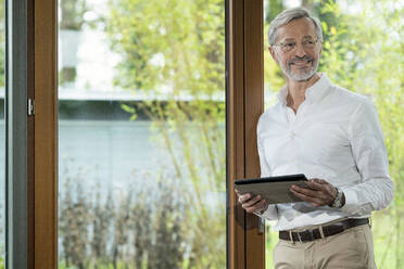 Smiling senior man with grey hair in modern design living room standing at window holding tablet - SBOF02113