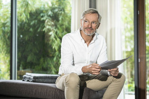 Smiling senior man with grey hair in modern design living room sitting on couch working on papers in home office - SBOF02116