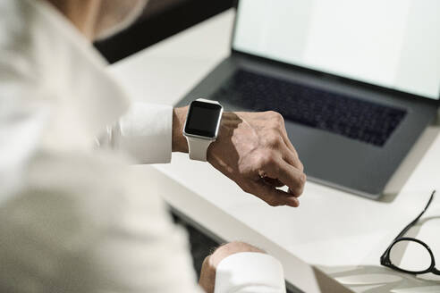 Close-up of senior man's hand with smartwatch and laptop - SBOF02122