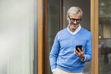 Smiling senior man with grey hair standing in front of his modern design home looking at smartphone - SBOF02125