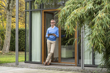 Senior man with grey hair standing in front of his modern design home holding tablet - SBOF02128