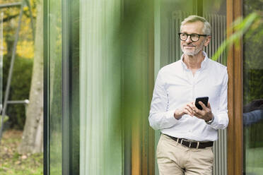 Smiling senior man with grey hair standing in front of his modern design home holding smartphone - SBOF02134
