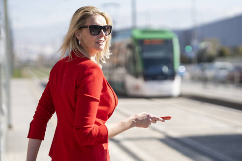 Blond businesswoman wearing red suit and waiting for the next train - JSMF01470