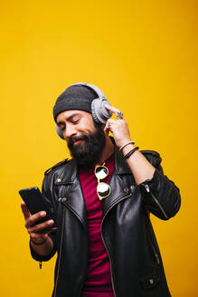 Portrait of a stylish young man in studio with smartphone and headphones - DGOF00479