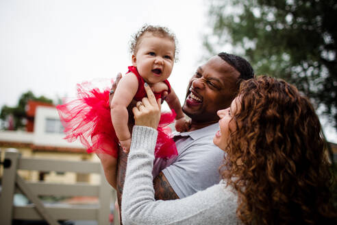 Biracial Couple Holding & Smiling at Baby - CAVF75479