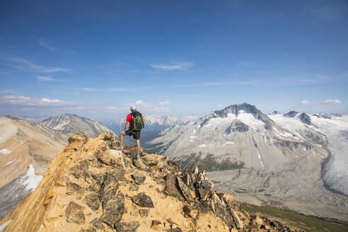 Backpacker standing on mountain summit. - CAVF75538