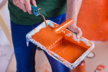 Close-up of man holding paint tray with orange paint - RTBF01422