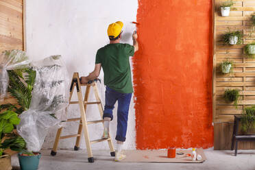 Rear view of man painting orange wall in his garden terrace - RTBF01425