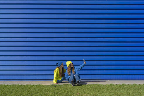 Two teenage girls wearing matching clothes taking selfie with smartphone in front of blue background - ERRF02677