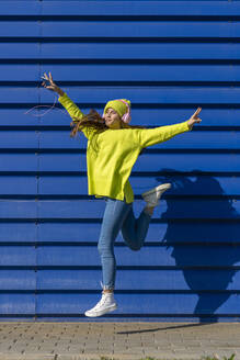 Happy teenage girl jumping in the air in front of blue background listening music with headphones - ERRF02698