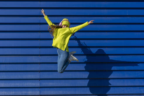 Teenage girl jumping in the air in front of blue background listening music with headphones - ERRF02701