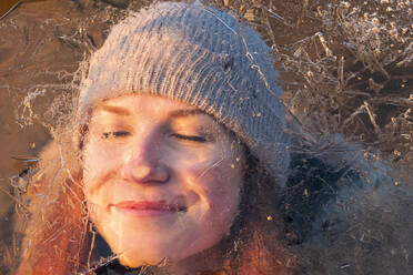 Portrait of smiling teenage girl behind ice-covered surface - LBF02903